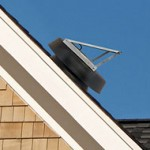 black solar attic fan on cedar shake home